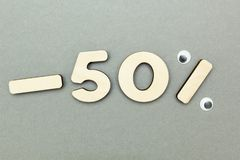 -50% sale of wooden figures on a gray paper background royalty free stock photo