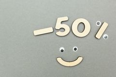 -50% sale of wooden figures on a gray paper background. Smiley royalty free stock photo