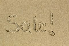 Sale word handwritten as text on sand in a beach Royalty Free Stock Photography