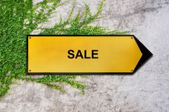 Sale on yellow sign hanging on ivy wall. Concrete texture close Stock Photography