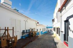 Salema村庄狭窄的街道  小村庄被粉刷的房子有海鲜餐馆的 法鲁,阿尔加威,南葡萄牙 免版税库存照片