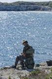 Salento峭壁的孤零零老渔夫 库存图片