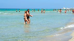 Holiday makers walk beach Torre San Giovanni crystalline waters Ionian sea. Salento, Italy, 13 Jul 2018 - holiday makers walk on beach of Torre San Giovanni in stock video