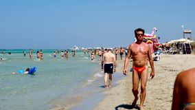 Salento holiday makers walk shore Torre San Giovanni beach crystalline waters Ionian sea. Salento, Italy, 13 Jul 2018 - holiday makers walk on the shore of the stock video footage