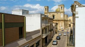 Salento - Taurisano church of Transfigurazion - Lecce province -. Salento, Italy, 17 Jul 2018 - cars pass in Via Roma among the Taurisano church of stock footage