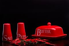 Salero, pimentero y mantequilla rojos en fondo oscuro de Cristina Arpentina Fotografía de archivo