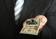 Sales agent offering a car. Sales agent offering car, holding a toy car and a dollar bill Stock Image
