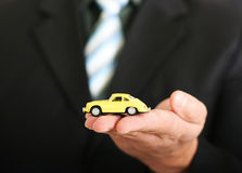 Sales agent offering a car. Sales agent offering car, holding a toy car Stock Photography