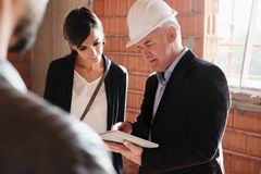 Sales Agent Showing New House To Husband And Wife. Sales agent talking with clients in new building. Man working as realtor in construction site with customers stock photography