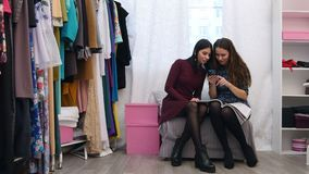 Sales assistant in clothing store helping to chose a customer new dress using smartphone and fashion magazine. Professional shot in 4K resolution. 056. You can stock video