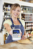 Sales Assistant In Food Store Handing Credit Card Machine To Cus Stock Photo