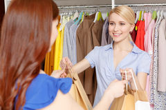 Sales assistant gives bags to the customer Stock Photos