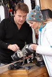 Sales Assistant Helping Advising Female Customer. On Ski Boots In Hire Shop Royalty Free Stock Image