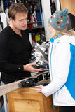 Sales Assistant Helping Advising Female Customer. On Ski Boots In Hire Shop Stock Images