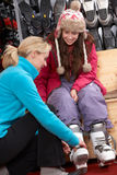 Sales Assistant Helping Teenage Girl. To Try On Ski Boots In Hire Shop Royalty Free Stock Image