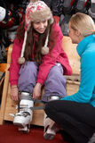 Sales Assistant Helping Teenage Girl. To Try On Ski Boots In Hire Shop Royalty Free Stock Photo