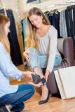 Sales assistant helping woman try shoe Stock Image