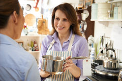 Sales Assistant In Homeware Shop Showing Customer Pan Royalty Free Stock Photo