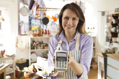Sales Assistant In Homeware Store With Credit Card Machine Royalty Free Stock Images
