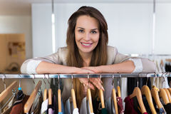 Sales assistant leaning on a clothing rail Royalty Free Stock Photos