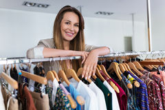 Sales assistant leaning on a clothing rail Stock Image