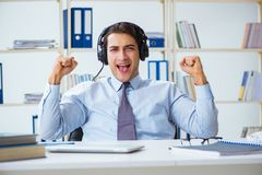 The sales assistant listening to music during lunch break. Sales assistant listening to music during lunch break Royalty Free Stock Photo