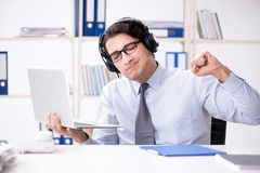 The sales assistant listening to music during lunch break. Sales assistant listening to music during lunch break Royalty Free Stock Image