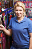 Sales Assistant In Pet Store With Display Of Dog Leashes Royalty Free Stock Image