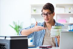 The sales assistant at publishing house showing ready printed books. Sales assistant at publishing house showing ready printed books Royalty Free Stock Images