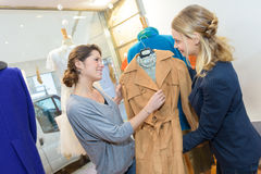 Sales assistant showing coat to customer in clothes shop Stock Photos