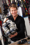 Sales Assistant With Ski Boots In Hire Shop. Smiling Stock Photography