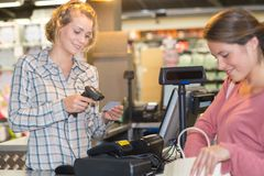 Sales assistant working at check-out. Sales assistant working at the check-out stock photography