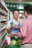 Sales clerk assisting man in supermarket, Beijing Stock Images