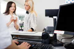 Sales Clerk Assisting Woman In Pharmacy. Sales clerk showing a product to young women at checkout counter in pharmacy Stock Photo