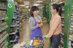 Sales clerk assisting women, holding jar in the supermarket, Beijing stock image