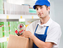 Sales clerk with cardboard box Royalty Free Stock Photos