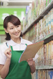 Sales Clerk Checking Groceries in Supermarket Stock Photography