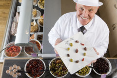 Sales clerk displaying specialty olives Royalty Free Stock Photo