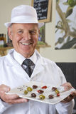 Sales clerk displaying specialty olives Royalty Free Stock Image