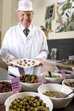 Sales clerk displaying specialty olives Stock Images