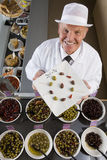 Sales clerk displaying specialty olives Royalty Free Stock Photos