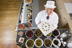 Sales clerk displaying specialty olives Stock Photography