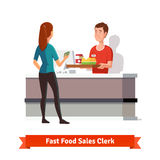 Sales clerk handing tray to a woman customer Royalty Free Stock Images