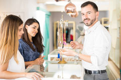 Sales clerk selling some jewelry Royalty Free Stock Image
