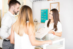 Sales clerk showing jewelry to a couple Royalty Free Stock Photos