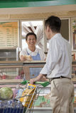 Sales Clerk smiling and assisting man at the Deli counter in the supermarket Stock Image