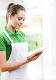 Sales clerk with tablet. Young female sales clerk working with digital tablet at supermarket Royalty Free Stock Image
