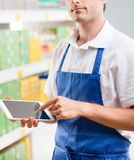 Sales clerk with tablet. Young sales clerk holding a digital tablet and working at supermarket Royalty Free Stock Photos