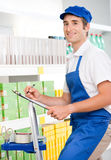 Sales clerk at work on a ladder Royalty Free Stock Photo
