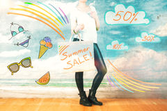 Sales concept. Side view of stylish girl at the beach holding shopping bag with summer sale text and other drawings. Sales concept Stock Photos